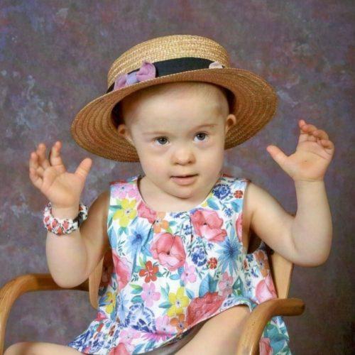 Lucinka, dívka sDownovým syndromem všatičkách akloboučkem na hlavě