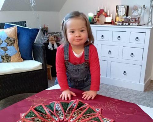 Lucinka sDownovým syndromem, fotka po léčbě sdelšími vlásky, doma