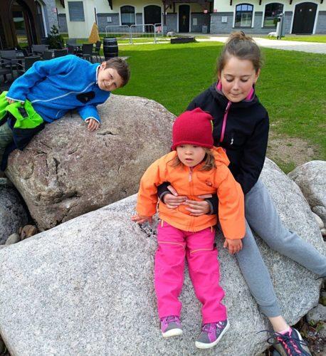 Lucinka, 5 let, dívka potýkající se sDownovým syndromem aleukémií, sbratrem asestrou sedící na venku na velkých kamenech